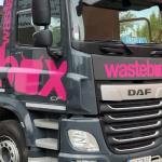 Der erste LKW im wastebox Design in den Farben Schwarz und Pink von schräg vorne auf einem Parkplatz mit Bäumen im Hintergrund