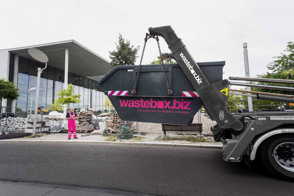 wastebox Lkw beim Abladen einer Mulde an einer Baustelle mit einem fachkundigen Mitarbeiter und Gebäude im Hintergrund