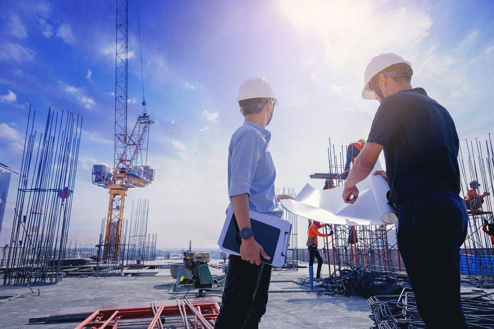 zwei Herren auf einer Baustelle mit Helmen und Plan besprechen die Abfallentsorgung der Baustelle via wastebox