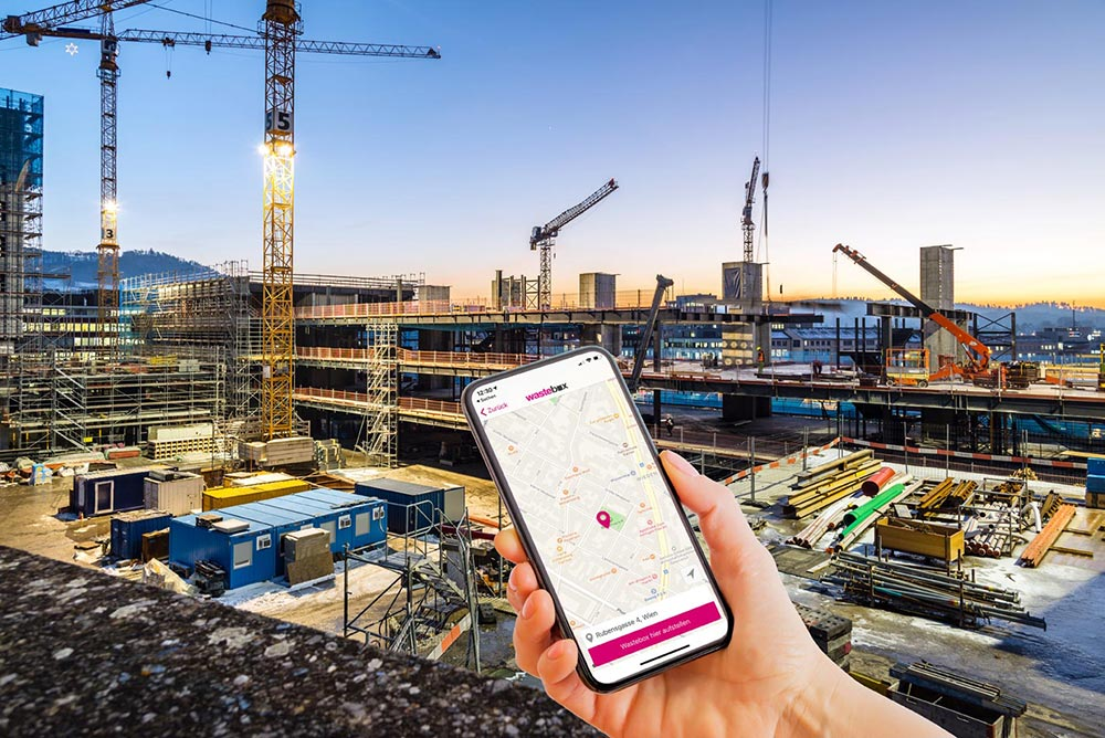 Bild einer Großbaustelle mit Kränen und Baucontainern im Dämmerlicht mit Ansicht der wastebox App für Entsorgung auf einem Smartphone im Vordergrund