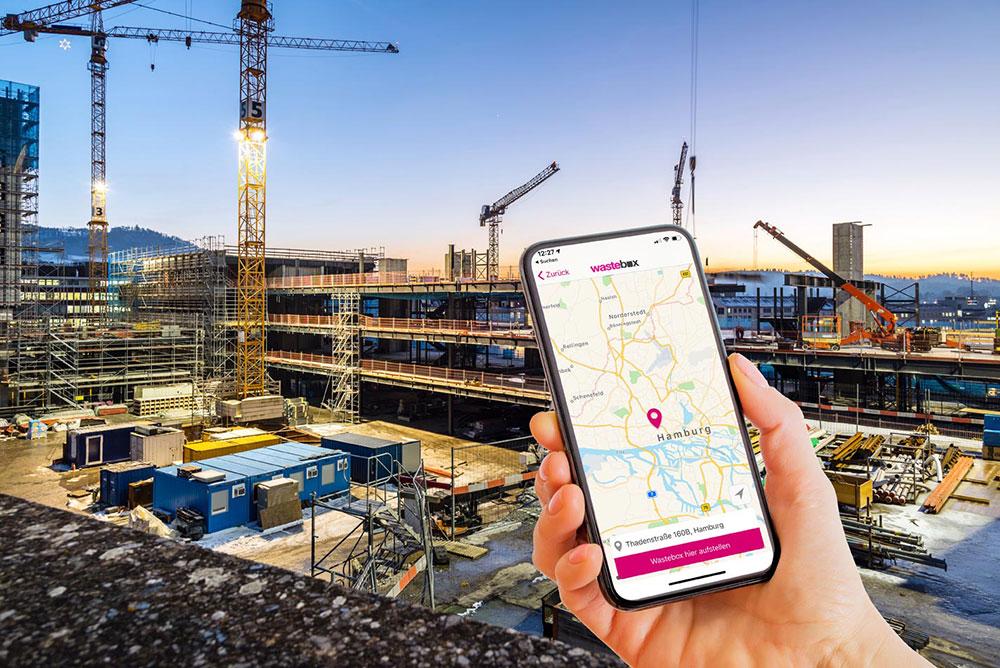 Smartphone mit wastebox App vor einer Großbaustelle