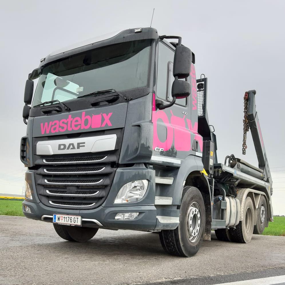 Der erste LKW im wastebox Design in den Farben Schwarz und Pink von schräg vorne auf einem Parkplatz mit Wiese im Hintergrund