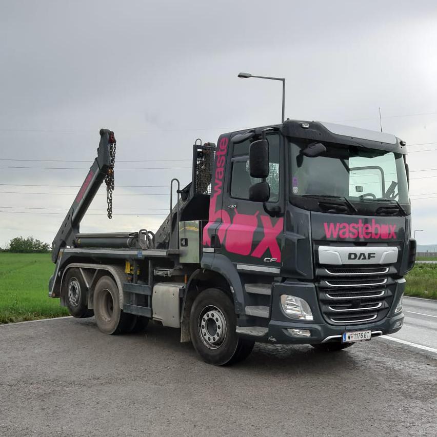 Der erste LKW im wastebox Design in den Farben Schwarz und Pink auf einem Parkplatz mit Wiese im Hintergrund